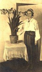 Mājturības stundās apgūto prasmju demonstrēšana - audzēkne pašdarinātajā tautas tērpā pie pašas izaudzētās puķes. Foto ap 1930.gadu.