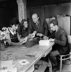 """Kolhoza """"Ādaži'' suvenīru darbnīcas vadītājs ar darbiniekiem apspriež suvenīru paraugus. 1968.gads."""