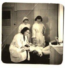 Medicīnas personāls pie slimnieka gultas. Stāv 1.no labās - māsa A.Milliņa. Foto ap 1957.gadu.